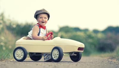 Kleiner Junge im Spielzeug VW Polo mit Autoversicherung